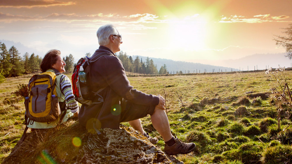 Retired couple enjoying a sunset while hiking